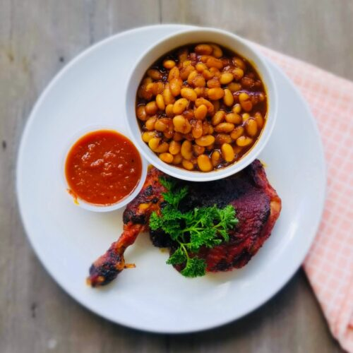 Smoked BBQ chicken leg quarters with baked beans