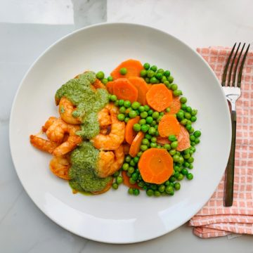 Pesto shrimp served with carrots and peas