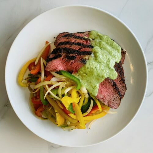 Grilled flank steak with sauteed pepper and onion